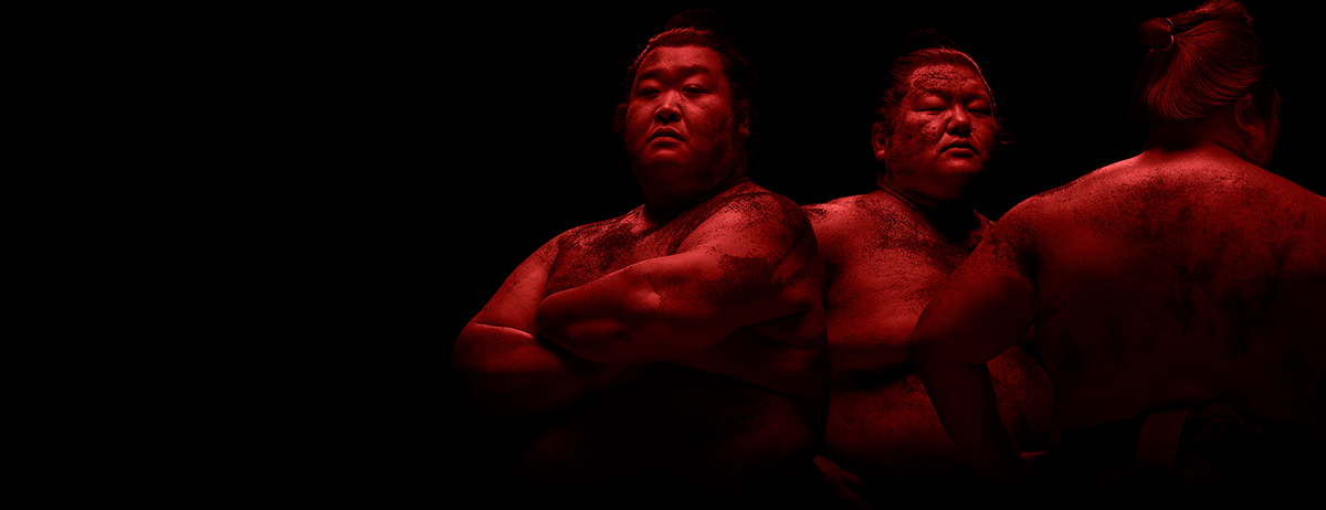 Group of sumos in red lighting on black background