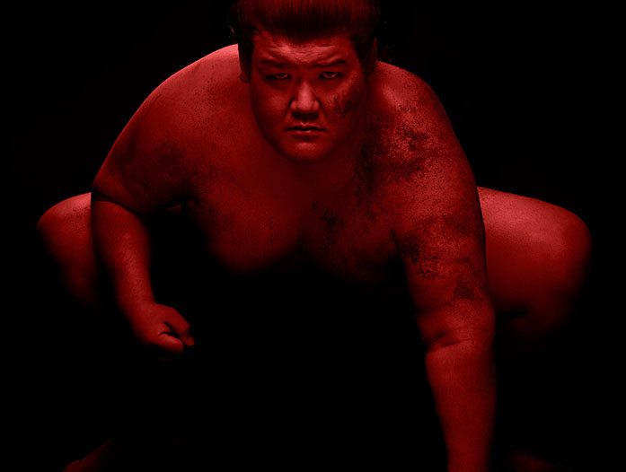 Sumo on in red light on black background